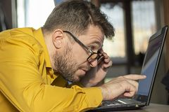 The bearded man with glasses buried his face in amazement in the laptop screen. stock image