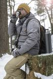 Bearded man in glasses with a camera and a backpack sitting on a. Handsome, bearded man in glasses with a camera and a backpack sitting on a tree stump in the Stock Photo