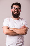 Bearded man in glasses with crossed hands look at camera. On white Stock Photos