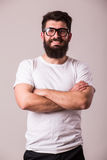 Bearded man in glasses with crossed hands look at camera. On white Stock Images