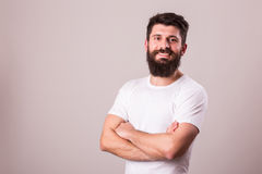 Bearded man in glasses with crossed hands look at camera. On white Royalty Free Stock Photo
