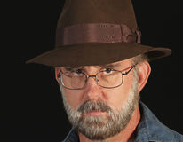 A Bearded Man in Glasses and a Fedora. A Bearded Man in Silver Wire Frame Glasses and a Brown Fedora Royalty Free Stock Photo