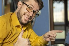 Bearded man with glasses with a happy face points to the laptop screen. royalty free stock images