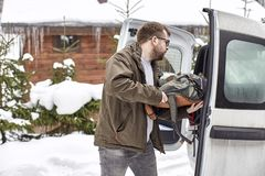Bearded man in glasses puts things in the trunk of a car, agains Royalty Free Stock Photography