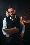 Bearded man in glasses reads handwritten text. Portrait of seriuos bearded man in glasses reads handwritten text. Desk with retro lighting lamp on background Royalty Free Stock Photography