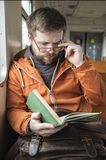 Bearded man with glasses rides on the train home from work and r. Handsome, bearded man with glasses rides on the train home from work and read with interest the Stock Image