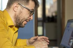 Bearded man with Glasses Sitting at home at the Table and Looking at the Laptop. stock photos