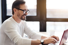 Bearded man with glasses working on laptop. Answering emails. Happy bearded man with glasses on using laptop while sitting against big window Stock Photo