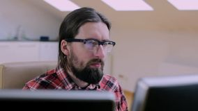 Bearded man in glasses working in office with 2 monitors. 2 stock footage