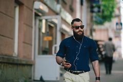 Bearded man goes and listens to music Royalty Free Stock Photo