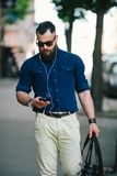 Bearded man goes and listens to music Stock Photography