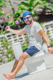 The bearded man in goggles astride the toilet, which is installe Stock Photos