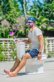 The bearded man in goggles astride the toilet, which is installe Royalty Free Stock Image