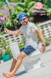 The bearded man in goggles astride the toilet, which is installe Stock Images
