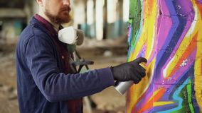 Bearded man graffiti painter is using aerosol paint to decorate pillar in old industrial building. Modern urban art. Handsome bearded man graffiti painter is stock video footage