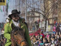 Bearded man in green jacket rides horse stock images