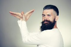 Bearded man with hands in bird shape Stock Images