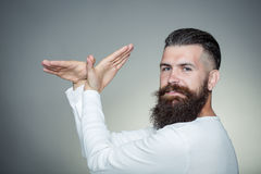Bearded man with hands in bird shape Royalty Free Stock Photo