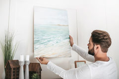 Bearded man hanging picture on wall at home