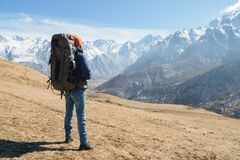 A bearded man in a hat and a backpack is standing outdoors against the snowy mountain peaks on a sunny day. Back view.  stock photo