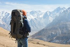 A bearded man in a hat and a backpack is standing outdoors against the snowy mountain peaks on a sunny day. Back view.  royalty free stock photography