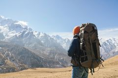 A bearded man in a hat and a backpack is standing outdoors against the snowy mountain peaks on a sunny day. Back view.  royalty free stock image