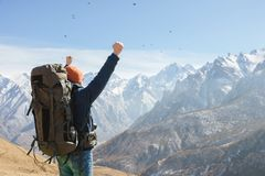 A bearded man in a hat and a backpack is standing outdoors against the snowy mountain peaks on a sunny day. View from. Behind. Hands up gesture of victory royalty free stock photos