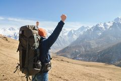 A bearded man in a hat and a backpack is standing outdoors against the snowy mountain peaks on a sunny day. View from. Behind. Hands up gesture of victory stock photo