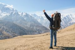 A bearded man in a hat and a backpack is standing outdoors against the snowy mountain peaks on a sunny day. View from. Behind. Hands up gesture of victory royalty free stock image