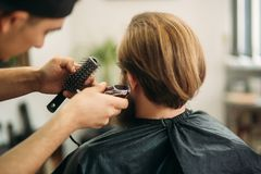 Bearded Man having a haircut with a hair clippers. Back view. Bearded Man having a haircut with a hair clippers stock images