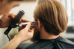 Bearded man having a haircut with a hair clippers. Closeup view with shallow depth of field royalty free stock photos