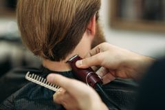 Bearded man having a haircut with a hair clippers. Closeup view with shallow depth of field stock photography