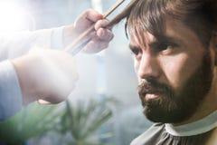 Bearded man having his hair cut stock photography