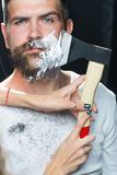 Bearded man having shaved. Portrait closeup young handsome sensual bearded man having shaved scrape chin with chopper foam frown studio play of light and shadow Stock Photography