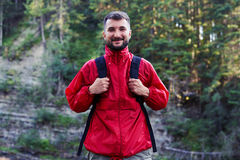 Bearded man hiker posing with backpack. Close-up shot of stylish bearded man with backpack posing at camera in mountains Royalty Free Stock Photography