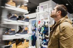 Man hipster in beige jacket choosing yellow winter boots in store - shopping, fashion, sale, ,style and people concept. Bearded man hipster in beige jacket Stock Images