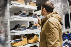 Man hipster in beige jacket choosing yellow winter boots in store - shopping, fashion, sale, ,style and people concept. Bearded man hipster in beige jacket Royalty Free Stock Images