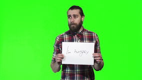 Bearded man hold i am hungry sign. Bearded man in a plaid shirt holds up a i am hungry sign at the camera over a green background with copy space stock footage