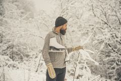 Bearded man hold skate in snowy winter forest, christmas. Bearded man hold hand up with skate in snowy winter forest at christmas holiday, winter sport and rest royalty free stock photography