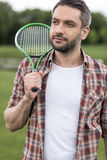 Bearded man holding badminton racquet on shoulder and looking away Royalty Free Stock Photo