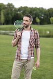 Bearded man holding badminton racquet on shoulder and looking away Stock Photography