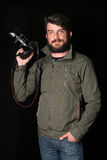 Bearded man holding camera in his arm. Close up. Black background Royalty Free Stock Photo