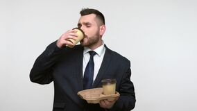 Bearded man holding disposable cups with coffee, drinking.