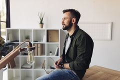 Bearded man holding eyeglasses while sitting at table and looking away Royalty Free Stock Photos