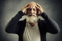 Bearded man holding his head and wincing in pain. Emotional bearded man holding his head and wincing in pain over grey background Royalty Free Stock Image