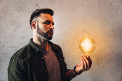 Bearded man holding illuminated light bulb while standing near grey wall Stock Photos