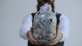 Bearded man holding a jar full of money isolated on white background. Getting rich. Clever storage of big money. Savings