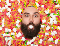 Bearded man holding marshmallow in mouth Stock Photography