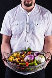 Bearded man holding a metallic basket with fresh vegetables Stock Photo