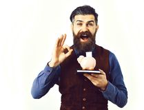 Bearded man holding notepad and moneybox with happy face. Bearded man, long beard, brutal caucasian hipster with moustache holding notepad and moneybox with Royalty Free Stock Image